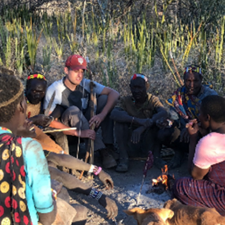 A student sits in a circle of native Hadza people in Tanzania.