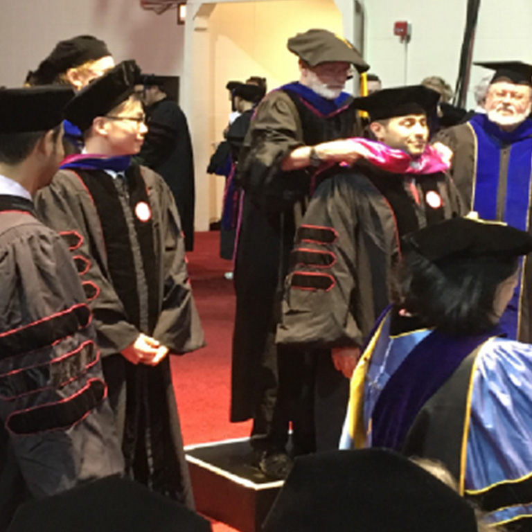 Faculty members get ready for an event in their ceremonial robes.